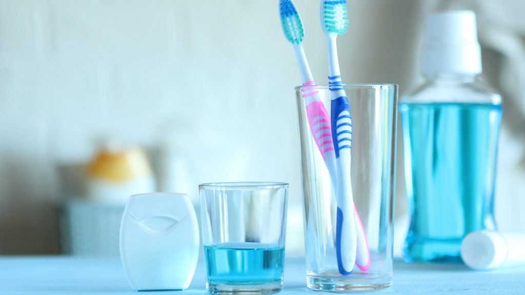 Cup with toothbrushes inside next to mouthwash and floss