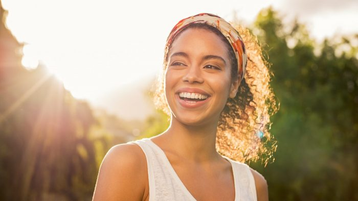 Young woman smiling with the sun behind her