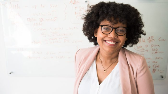 Woman Wearing Glasses Smiling In Front Of A Whiteboard